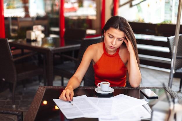 頭痛。のコーヒーを飲みながらカフェに座っている女の子。作業環境。間違いの失望