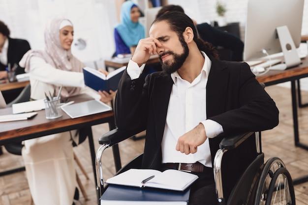 オフィスの頭痛車椅子の男障害者。
