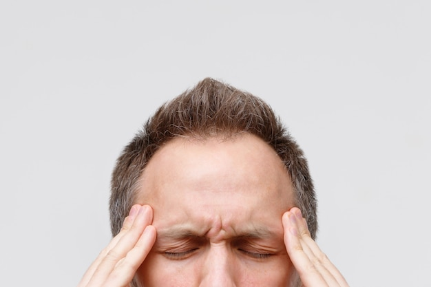 Headache, nervous tension, temporal and throbbing pain concept. close up portrait of man massaging his temples, closed eye, isolated on gray background. strong migraine