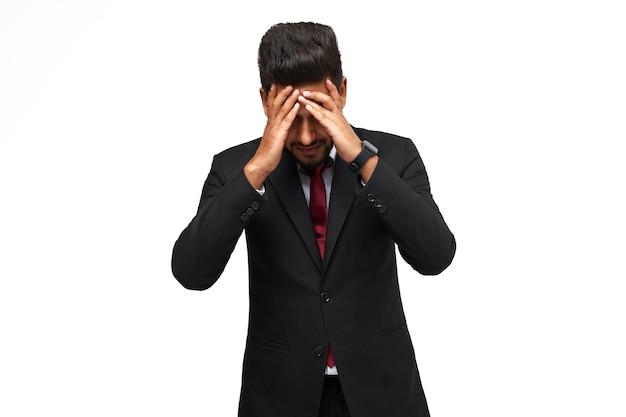孤立した白い背景の上のスーツを着たインドのビジネスマンの頭痛。