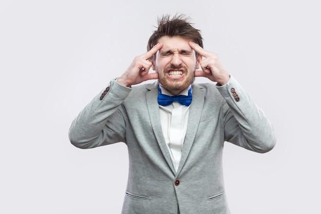 頭痛。カジュアルな灰色のスーツと青い蝶ネクタイで立って、歯を食いしばって彼の痛みを伴う頭を保持している病気や心配のひげを生やした男の肖像画。明るい灰色の背景に分離された屋内スタジオショット。