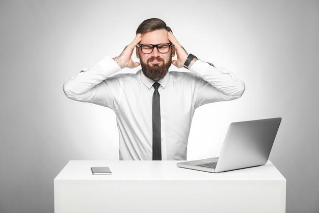 Головная боль. портрет нездорового болезненного молодого менеджера в белой рубашке и черном галстуке сидит в офисе и сильно болит голова, держа пальцы возле висков. студия выстрел, изолированные, серый фон