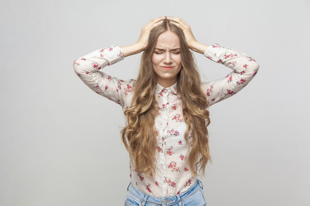 彼女の頭に触れて片頭痛を持っている頭痛不幸なブロンドの女の子