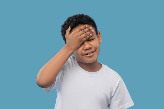 두통. 그의 이마에 손을 만지고 닫힌 눈을 가진 불행한 어두운 피부의 초등학생 소년