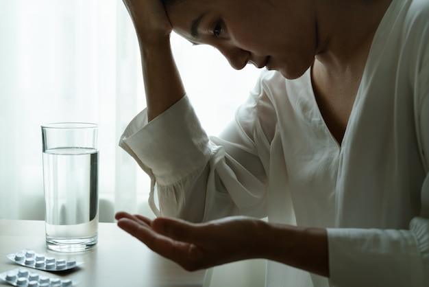 Headache women hand hold medicine with a glass of water