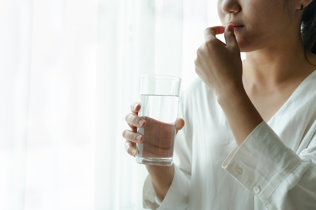 Headache women take medicine with a glass of water