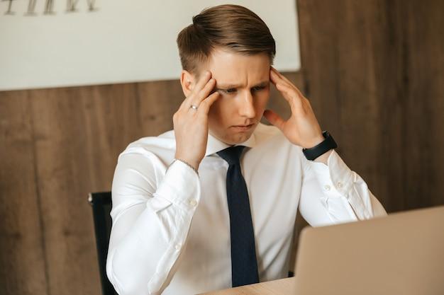 두통, 업무량, 힘든 일, 직장에서 지친 남자. 컴퓨터에서 원격으로 작업합니다.