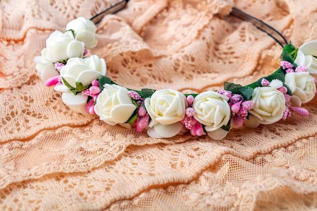 머리띠 또는 손의 화환은 흰색과 분홍색 꽃을 만들었습니다. 섬세한 상아색 레이스 천으로 된 빈티지 액세서리.