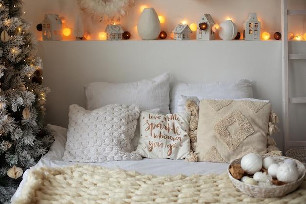 새해 베개와 크리스마스 장식, 빛나는 화환이 있는 헤드보드 침대