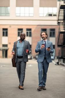 オフィスに向かっています。持ち帰り用のコーヒーを持ってオフィスに向かうスーツを着たビジネスパートナー
