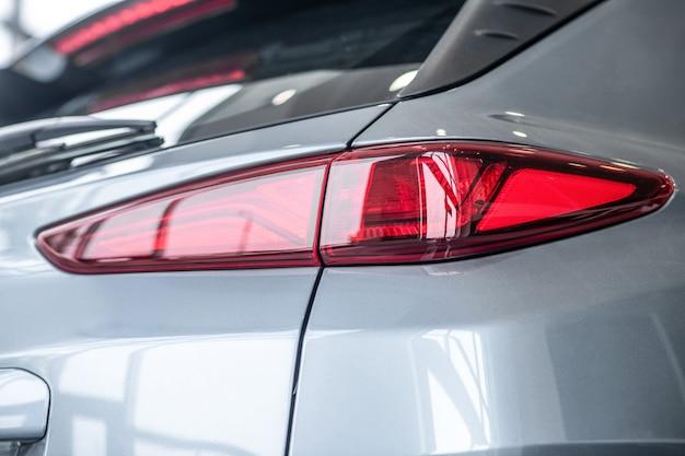 Фара, автомобиль. сверкающая красная фара нового серого легкового автомобиля. блестящий стильный автомобиль, отражающий дневной свет.