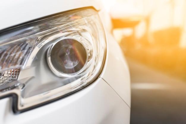 Headlight of new white auto on street