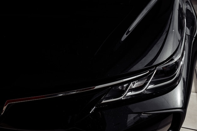 モダンな名門ブラックカーのヘッドライトをクローズアップ。現代の車の写真、ヘッドライトの詳細を閉じます。モダンでラグジュアリーなテクノロジーとオートディテールのヘッドライトカープロジェクターled。セレクティブフォーカス