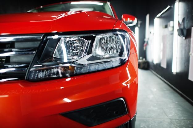 モダンなガレージにある素敵で新しいオレンジ色のスポーツsuv車のヘッドライト。 Premium写真