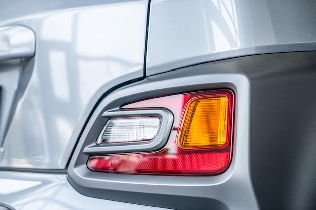 Фара, легковой автомобиль. крупный план задней фары нового блестящего чистого серого легкового автомобиля