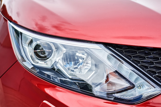 Headlight with halogen lamp on modern red car, close up