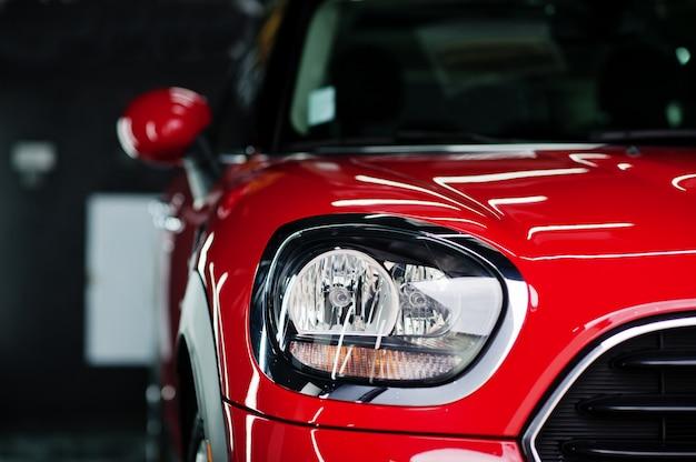 Фары и капот спортивного красного автомобиля в гараже