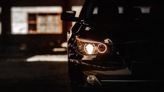 Headlights of black modern car close up modern luxury car closeup banner background