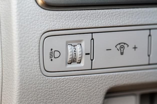 ヘッドライトコレクター調整ボタン。現代の車の黒いインテリアのビューを失います。