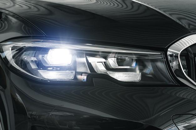 新しい白い高級車のヘッドライトがクローズアップ