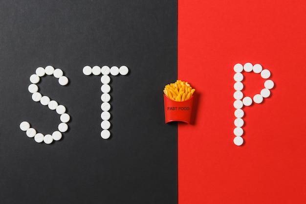 패스트푸드 금지. stop이라는 단어의 흰색 원형 정제, 빨간색 검정색 배경에 감자튀김이 분리된 상자. 건강, 선택, 건강한 생활 방식의 개념. 공간 광고를 복사합니다.