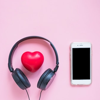 Headphone around the red heart shape and smartphone against pink backdrop