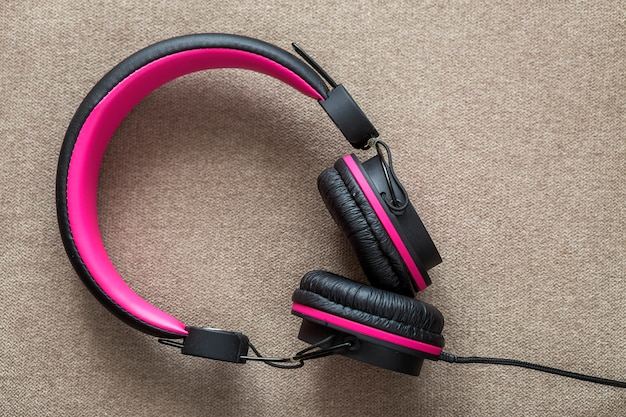 Headphone black and pink isolated on light cloth flat
