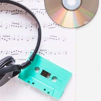 Headphone; compact disc and turquoise cassette on musical note over white background