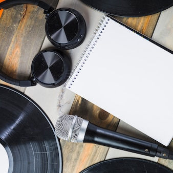 Headphone; microphone; vinyl record and blank spiral notepad on wooden table
