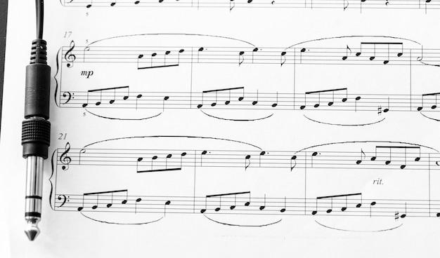 펜과 음악 시트가있는 헤드폰 플러그-음악적 배경
