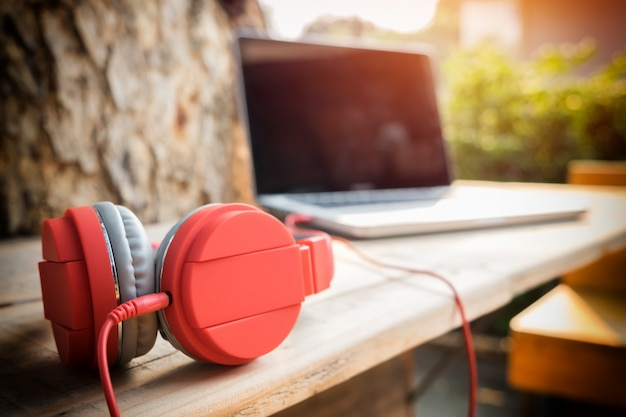 Headphone with laptop computer against defocused background, outdoor relax concept