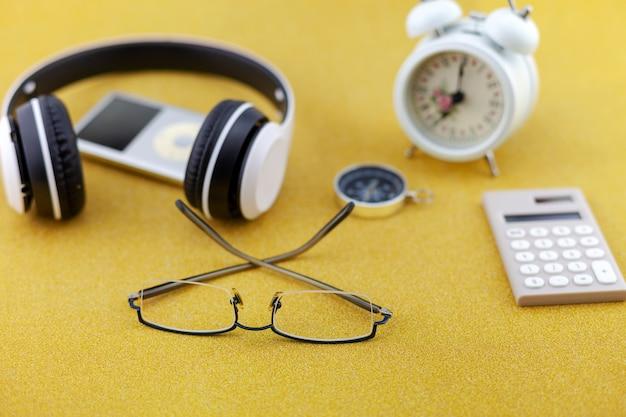 골드 반짝이 텍스처 반짝 반짝 종이 배경에 흰색 알람 시계, 나침반, 계산기와 헤드폰