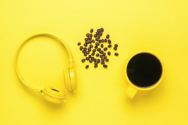 Наушники, чашка кофе и кофейных зерен на желтом фоне. утренние аксессуары.