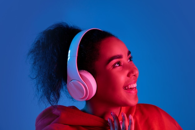 Headphones. african-american woman's portrait isolated on blue studio background in multicolored neon light. beautiful female model. concept of human emotions, facial expression, sales, ad, fashion.