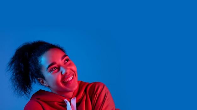 헤드폰. 여러 네온 불빛에 블루 스튜디오 배경에 고립 된 아프리카 계 미국인 여자의 초상화. 아름다운 여성 모델. 인간의 감정, 표정, 판매, 광고, 패션의 개념.