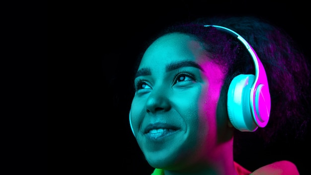 Наушники. портрет афро-американской женщины, изолированные на темном фоне студии в разноцветном неоновом свете. красивая женская модель. понятие человеческих эмоций, выражения лица, продаж, рекламы, моды.