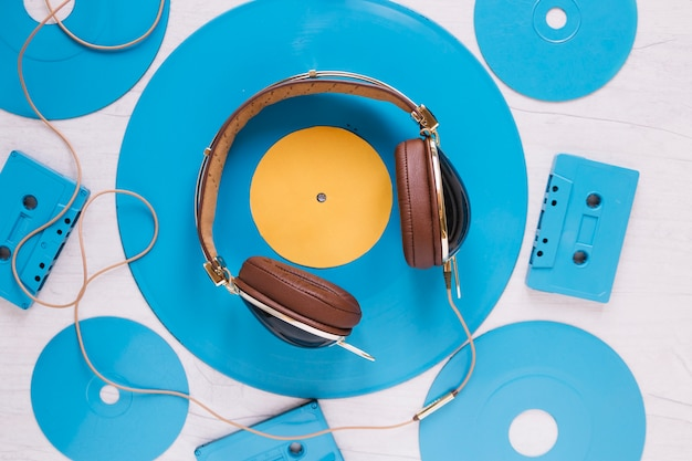 Cuffie in mezzo a dischi e cassette blu