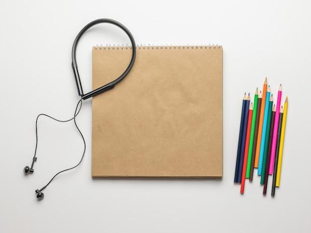 Наушники, открытый альбом для рисования и карандаши на белом фоне. аксессуары для творчества.
