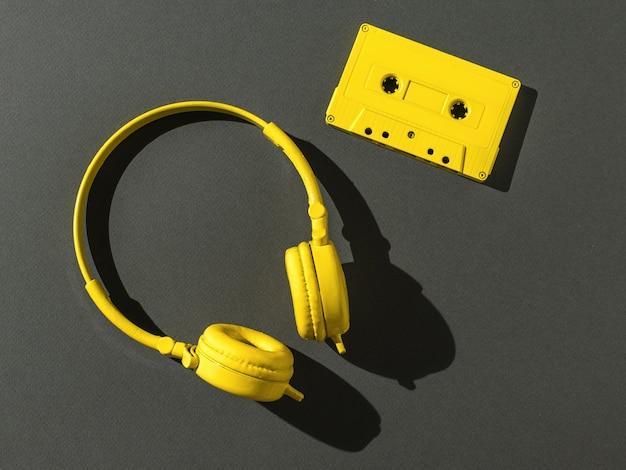 밝은 빛의 검정색 배경에 자기 테이프가 있는 헤드폰과 노란색 카세트. 컬러 트렌드. 플랫 레이.