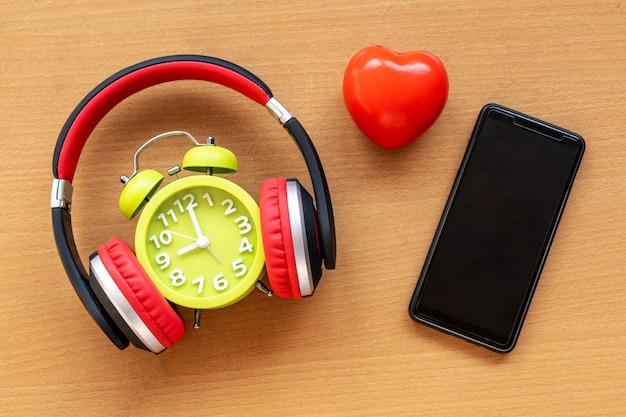 ヘッドフォン、目覚まし時計、スマートフォン、木製の机の上の赤いハート。音楽のコンセプト