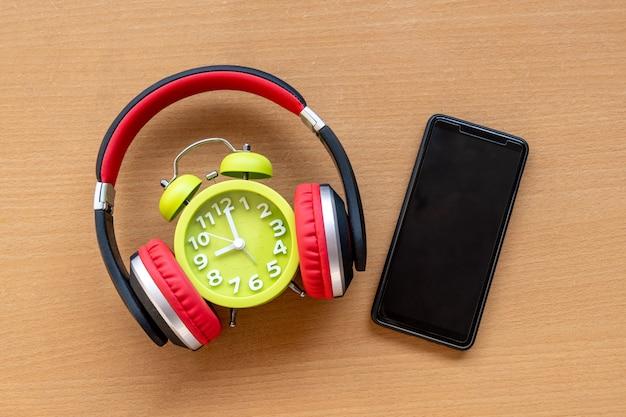 ヘッドフォン、目覚まし時計、木製の机の上のスマートフォン。音楽のコンセプト