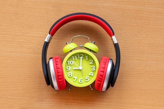 ヘッドフォンと木製の机の上の目覚まし時計。音楽のコンセプト
