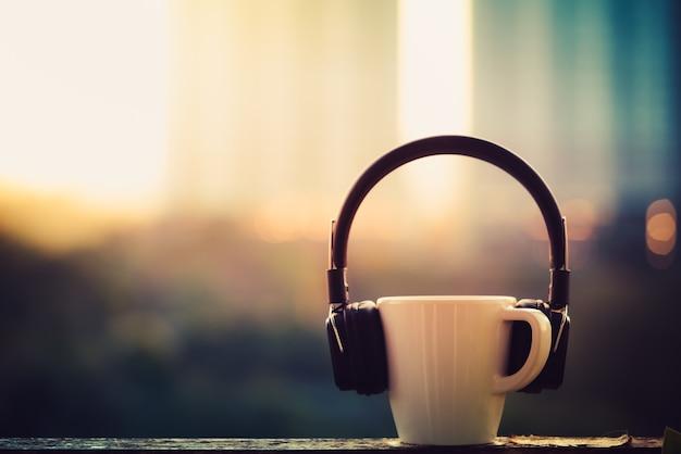 ぼやけた街のヘッドフォンとコーヒーカップ