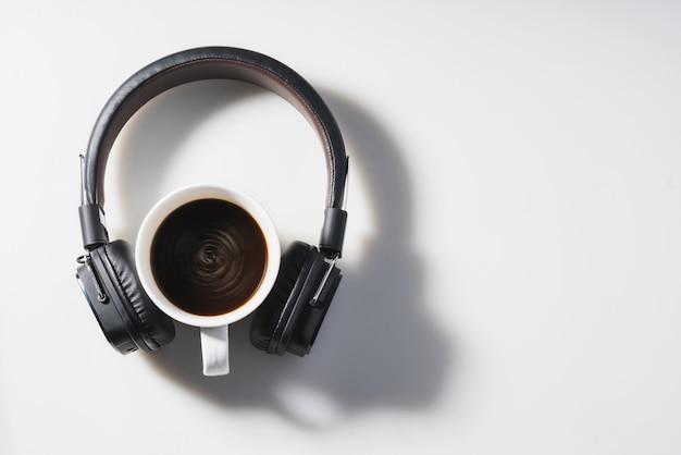 白いテーブルの上のヘッドフォンとコーヒーカップ。音楽のコンセプト。上面図