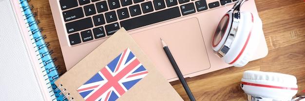 ノートパソコンのキーボードのクローズアップに横たわっているヘッドフォンと英語の教科書