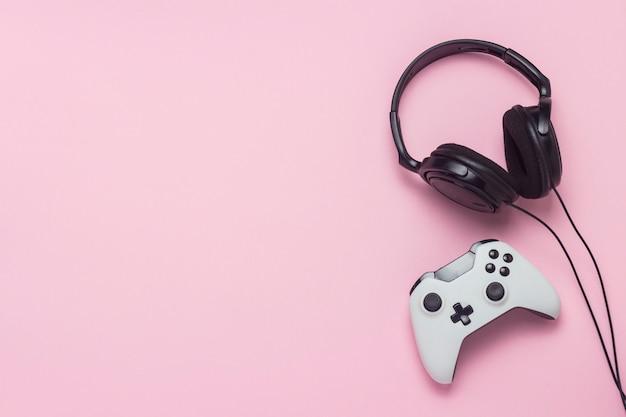 Наушники и геймпад на розовом фоне. концепция игры на консоли, развлечения, досуг, онлайн игры. плоская планировка, вид сверху.