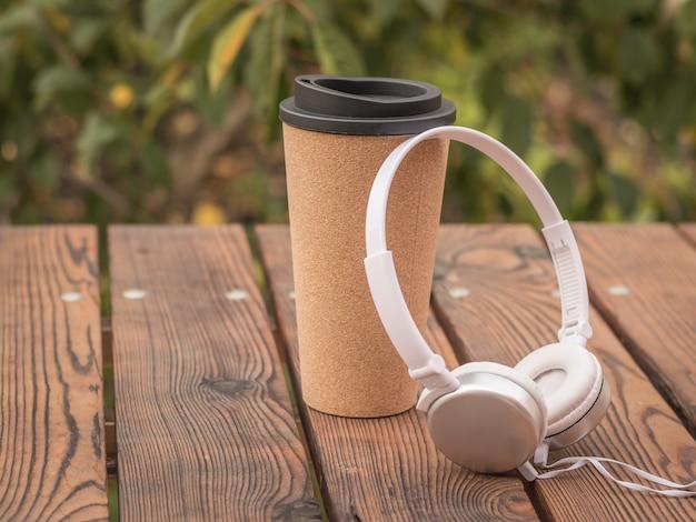 公園のテーブルにヘッドフォンとコーヒーグラス。秋のカフェで過ごす。