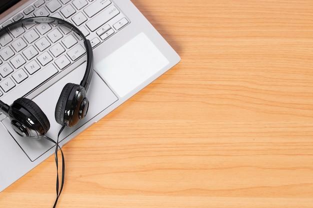 Наушники и ноутбук на деревянных фоне.