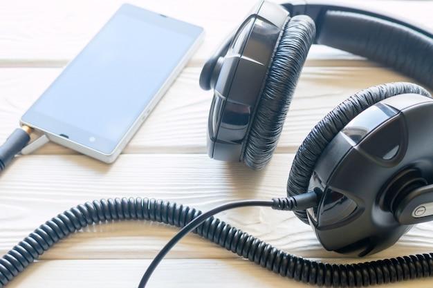 Наушники и мобильный телефон на белом фоне
