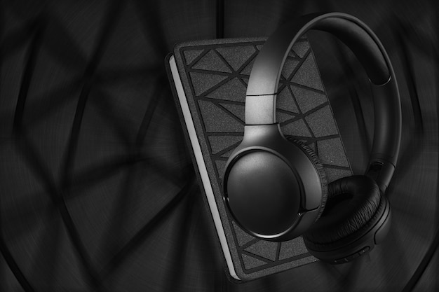 Наушники и ноутбук на темном фоне. концепция аудиокниги.